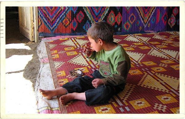 A little boy enjoys a tea-break at a Bedouin encampment