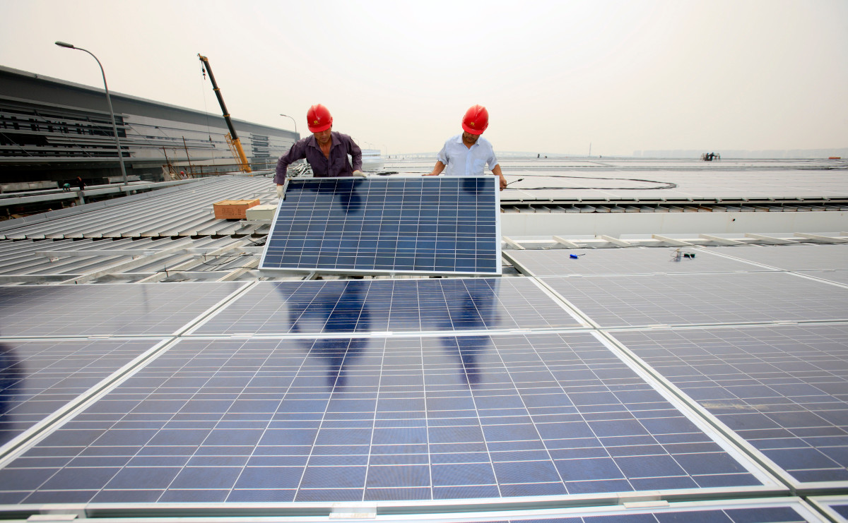 Trabalhadores instalando alguns dos 23.000 painéis solares fotoelétricos nos telhados do terminal de passageiros da estação ferroviária de Hongqiao, em Shanghai. © Jiri Rezac 2010 (CC BY-NC-SA 2.0)